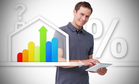light brown hair: Smiling man standing behind the energy efficient house graphics with question and percentage marks using tablet Stock Photo
