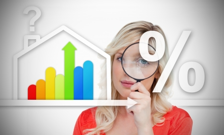 blonde blue eyes: Woman standing behind  energy efficient house graphic with question and percentage marks holding a magnifier Stock Photo