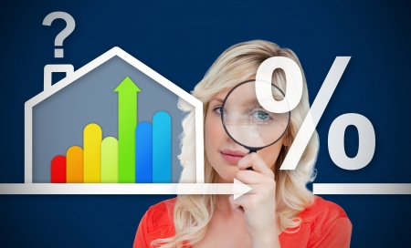 Woman looking through the magnifying glass standing against a background of  energy efficient house graphic with question and percentage marks photo
