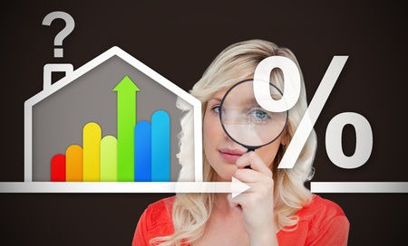 Woman looking into the camera through the magnifier against a background of energy efficient house graphic with question and percentage marks photo