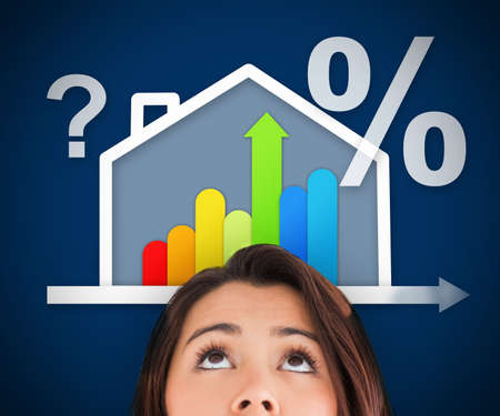 Woman standing against a blue background looking up at energy efficient house graphic with question and percentage marks photo