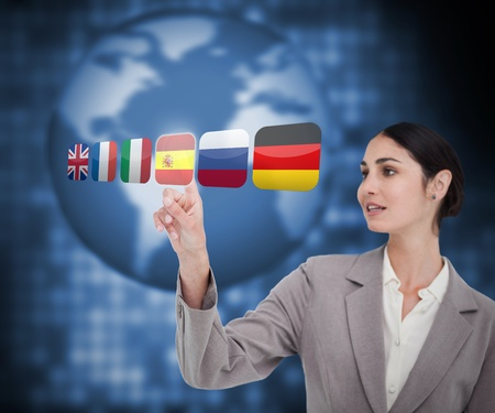 Woman in suit choosing Spanish flag on touch screen photo