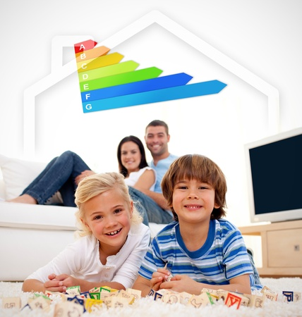 couch: Two smiling children lying on a carpet in the living room with parents with energy rating graphic Stock Photo
