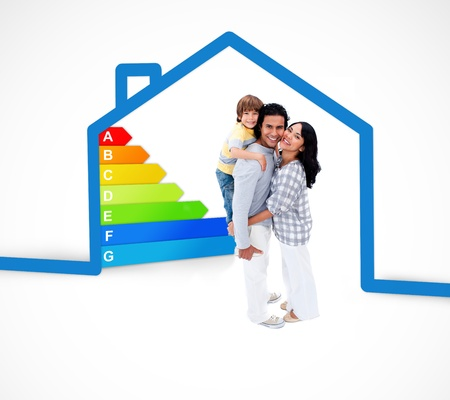 energy rating: Smiling family standing with a blue house illustration with energy rating on a white background Stock Photo