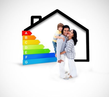 energy rating: Smiling family standing with a black house illustration with energy rating on a white background Stock Photo