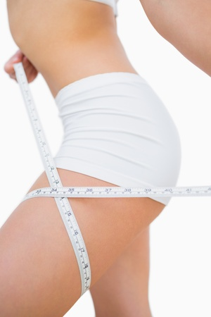 midsection: Midsection of woman measuring thigh with measuring tape over white background Stock Photo