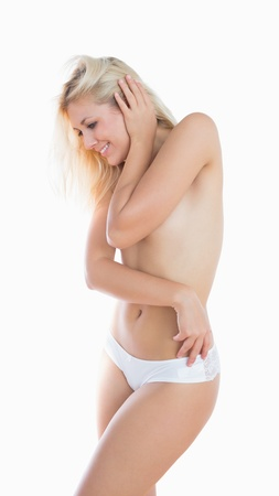 Topless young woman in panties smiling over white background photo