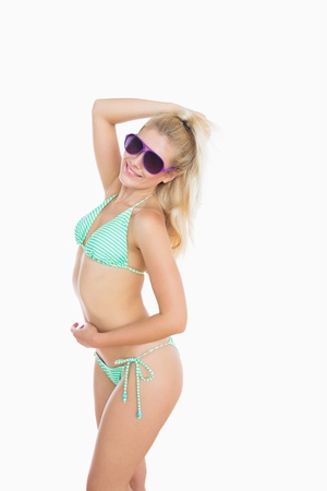 sensuous: Sexy young woman in bikini posing with sunglasses over white background