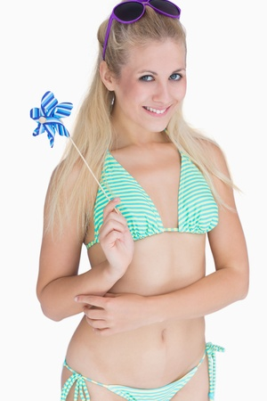 Portrait of happy young woman in bikini holding pinwheel over white background photo