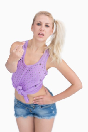 obscene: Portrait of young woman showing middle finger over white background Stock Photo