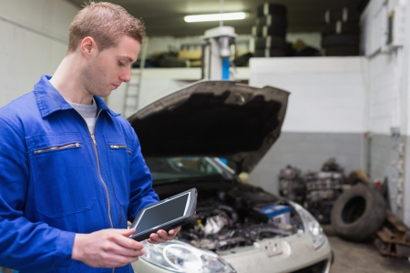 Young male mechanic with digital tablet at garage photo