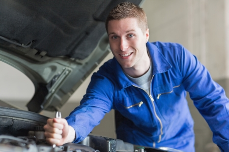 Portrait of young mechanic working on automobile engine Stock Photo - 18110494