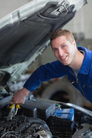 Portrait of happy male mechanic working on car engine Stock Photo - 18109525