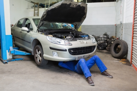 Maschio meccanico lavora sotto l'automobile in garage