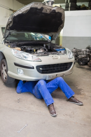 Male mechanic under car in garage Stock Photo - 18109836