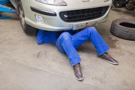 auto mechanic: Mechanic working under car in garage