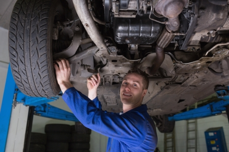 auto mechanic: Portrait of male auto mechanic working under car Stock Photo