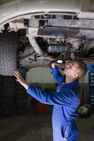Male mechanic examining car using flashlight in garage photo