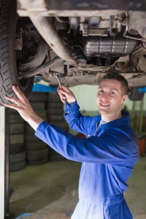 Portrait of male mechanic in coveralls working under car Stock Photo - 18109897