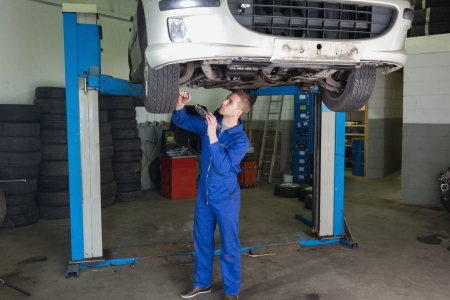 Male mechanic working under raised car in garage photo