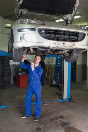 Full length portrait of male mechanic working under raised car in workshop photo