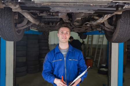 Portrait of male mechanic with clipboard under car photo