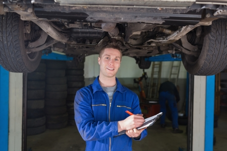 Portrait of male mechanic preparing checklist under car photo