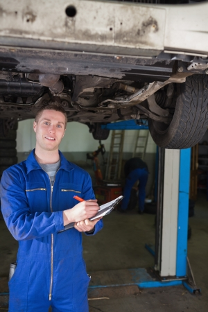 Portrait of male repairman preparing checklist under car photo