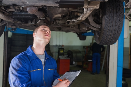 Young male mechanic under car writing on clipboard in workshop photo