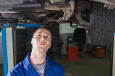 Male mechanic examining under car in workshop photo
