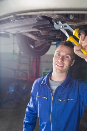 Portrait of happy male mechanic repairing car with pliers photo