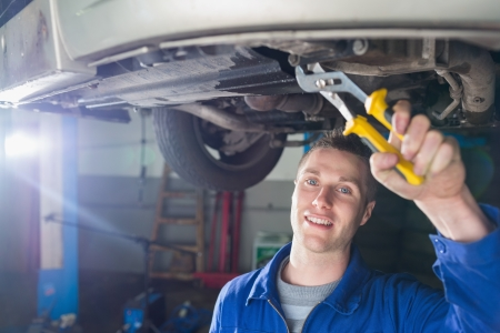 Portrait of happy male mechanic repairing car with pliers Stock Photo - 18109118