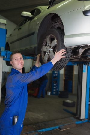 Car on hydraulic lift as mechanic examining tire in garage photo