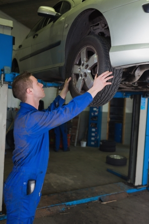 Side view of male mechanic examining car tire in workshop photo