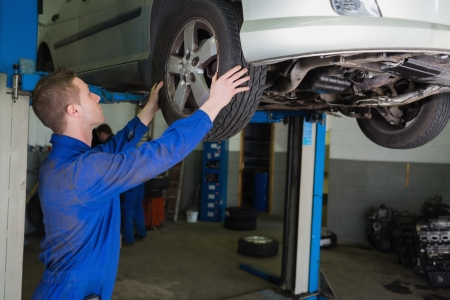 Auto mechanic examining car tire in garage photo