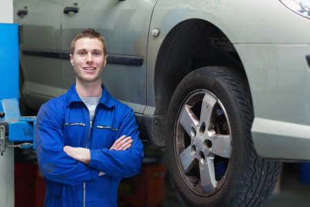 auto mechanic: Portrait of male mechanic with arms crossed standing by car Stock Photo