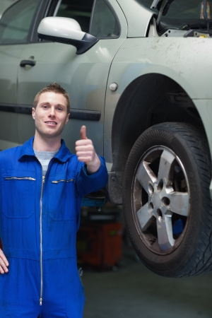 Portrait of  car mechanic gesturing thumbs up in workshop photo