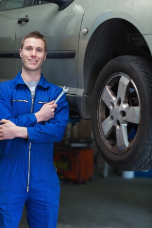 Portrait of young male mechanic with spanner standing by car Stock Photo - 18108378