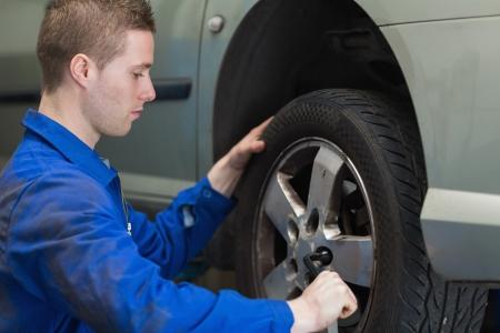 lug: Male mechanic changing car wheel with lug wrench Stock Photo