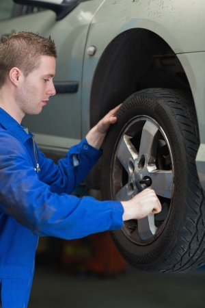 Male mechanic using lug wrench to change car tyre photo