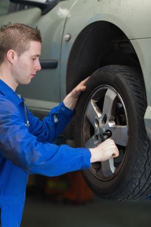 lug: Male mechanic using lug wrench to change car tyre