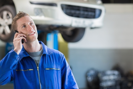 Auto mechanic using mobile phone in workshop photo