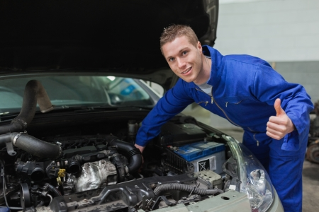 bonnet up: Portrait of mechanic under car bonnet gesturing thumbs up Stock Photo