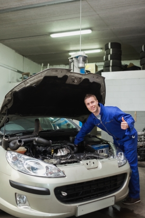 bonnet up: portrait of male mechanic by car giving thumbs up gesture