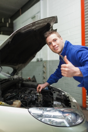 bonnet up: Portrait of auto mechanic gesturing thumbs up as he checks oil level of car Stock Photo
