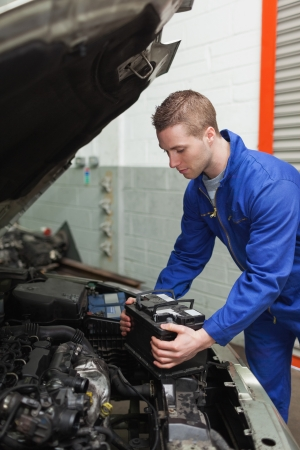car battery: Male mechanic checking car battery in workshop