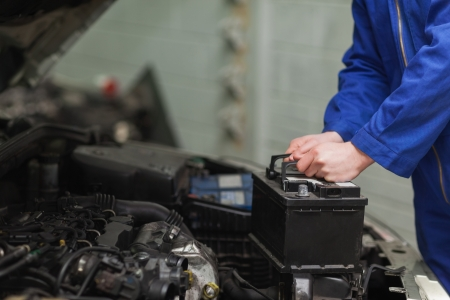bateria: Hombre mec�nico cambiar la bater�a del coche Foto de archivo