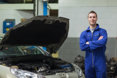 Portrait of confident mechanic standing by car with open hood photo