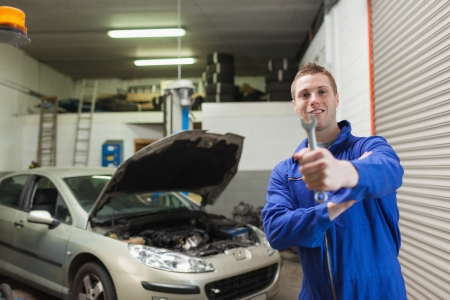 Portrait of young male mechanic offering spanner in worshop Stock Photo - 18109443