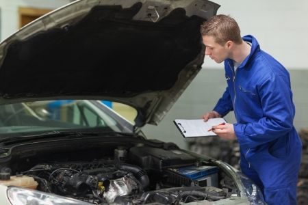 Male mechanic with clipboard examining car engine photo